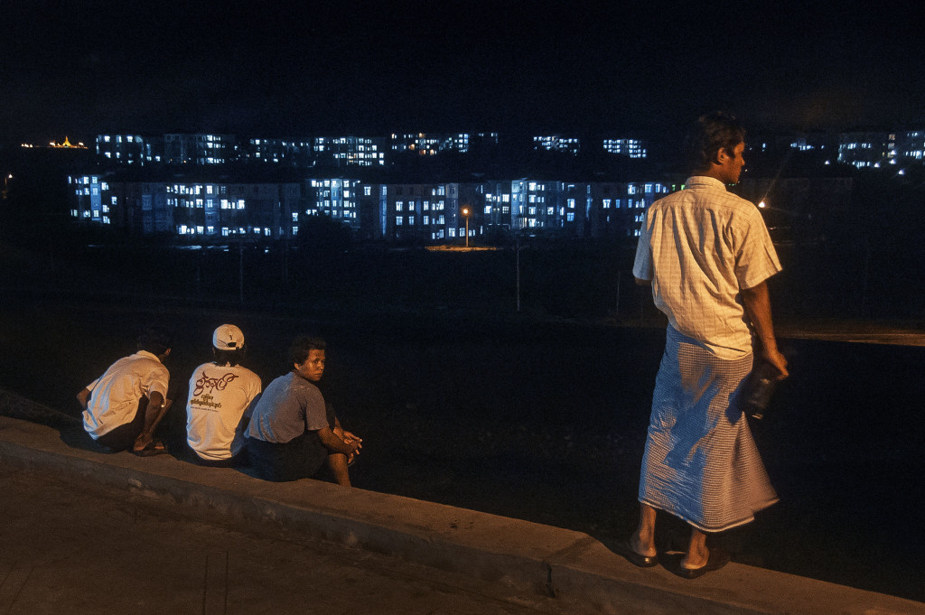 Overlook: Floor staff and kitchen boys look over the city from out the back doors of the restaurant strip. Naypyidaw enjoys a constant supply of electricity while the larger population hubs Rangoon and Mandalay sit in the dark for as many as twelve of every twenty-four hours.
