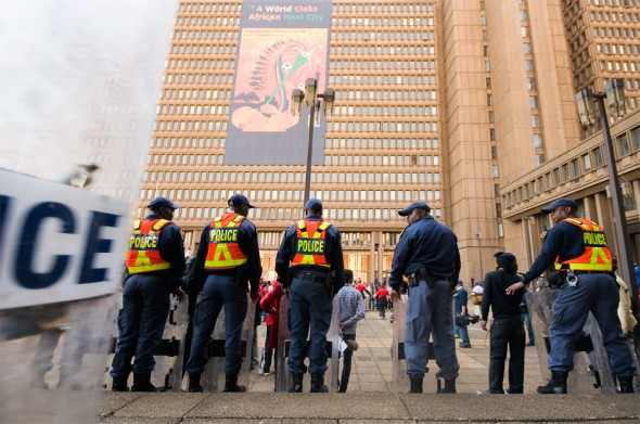 Johannesburg metro police set up a riot guard as protestors arrive at the municipal building for an address by the mayor and union leaders.