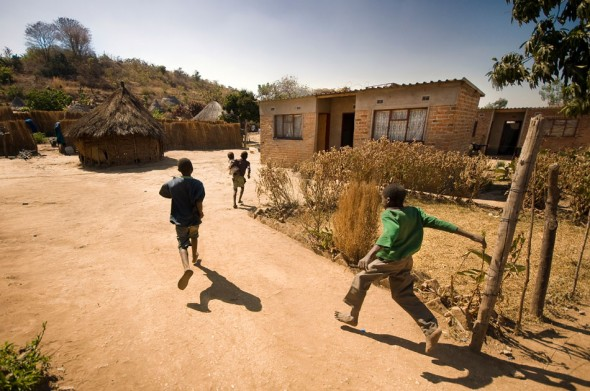 Foot traffic outside a new IOM-constructed brick house among traditional rondavels.