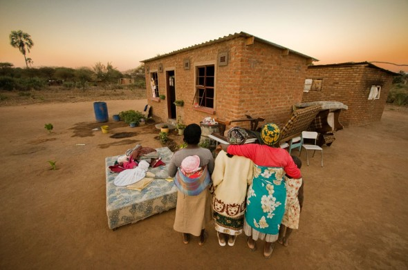 A family pauses midway through moving furniture into their new IOM-constructed house.