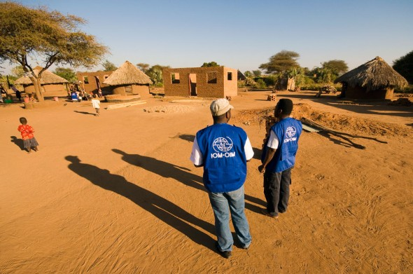 IOM vests supervise a construction site near Chiredzi. Here, local labour build their own homes from materials provided by IOM.