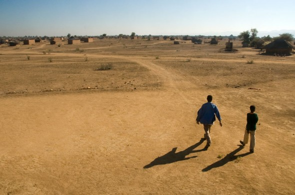 A father and son make their way through the home-specked flatlands off the grid in Zimbabwe's Eastern Highlands.