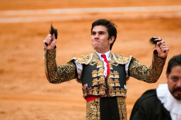 Victorious after the battle, the matador clenches his trophies: the ears of his opponent.