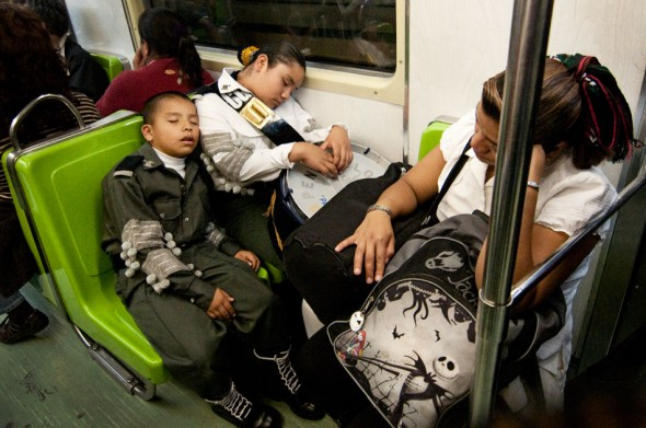 Still dressed in their uniforms, parade participants sleep on the late-service metro after the celebrations.