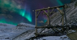 Lightscape: Aurora dance over the wooden carcass of an old mining tramway at the southern end of Longyearbyen. With a population of 2000, Longyearbyen is the only sizable pocket of humanity for 1000km in any direction, including north, where it&#039;s the last civilian settlement of any sort before the North Pole.