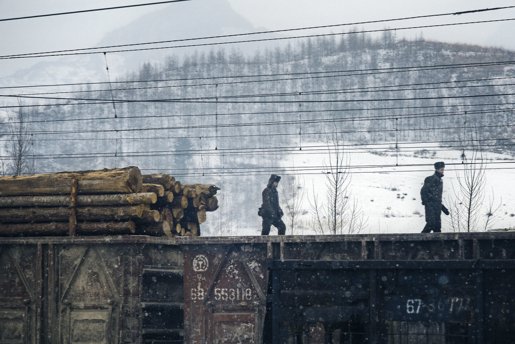 Timber Wolves: Soldiers walk the length of a freight train in a snowstorm in rural South Hamgyong province.