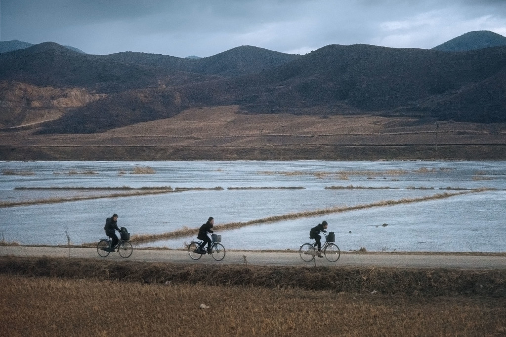 Three teenagers cycle past frozen rice paddies in rural North Hamgyong province.