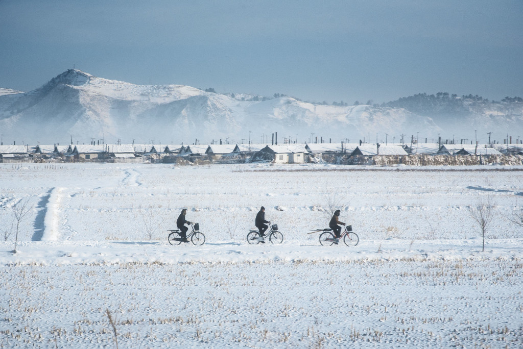 Six Wheel Drive: Villagers ride through the North Korean countryside near the Russian border in North Hamyong province as a coal-fired haze rises from the village behind them.