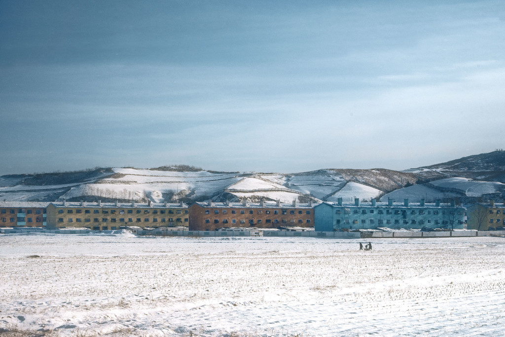 Winter Rainbow: Pastel-hued apartments form a border along potato fields.